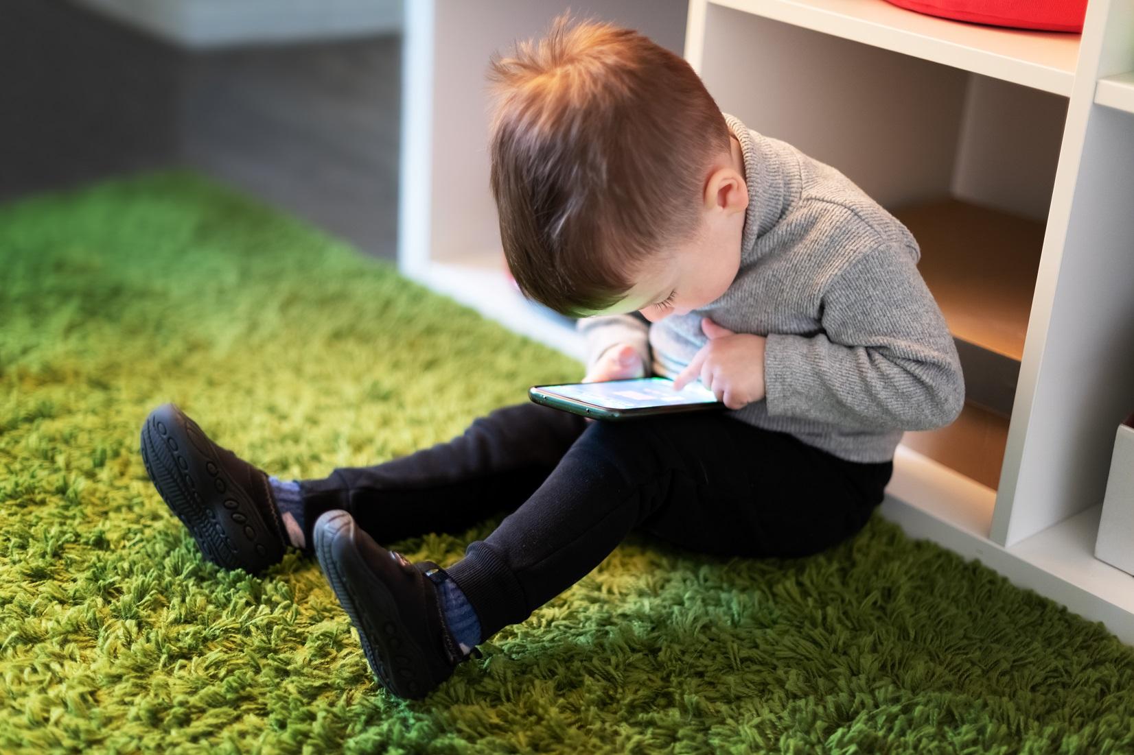 little boy play games on smartphone B9UACT7 Другая SOVA дети, психология