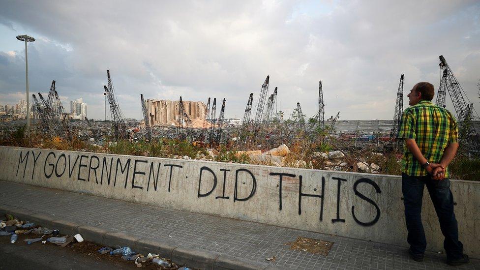 мужчина стоит и смотрит на разрушенный взрывом бейрут